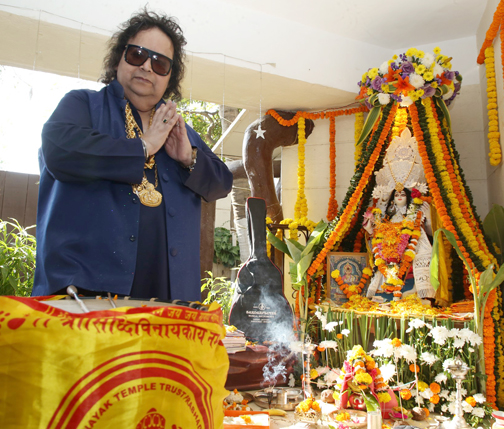 Bollywood singer, composer Bappi Lahiri poses for photographs during the Hindu festival celebrates ph at his house